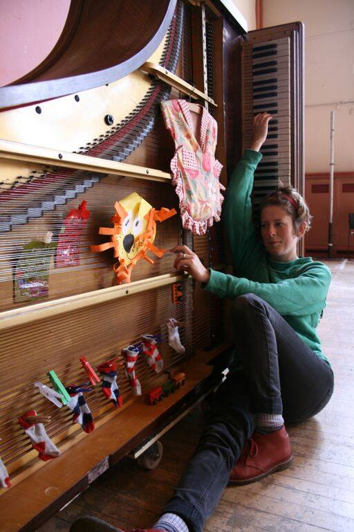 Sarah with piano and children's art