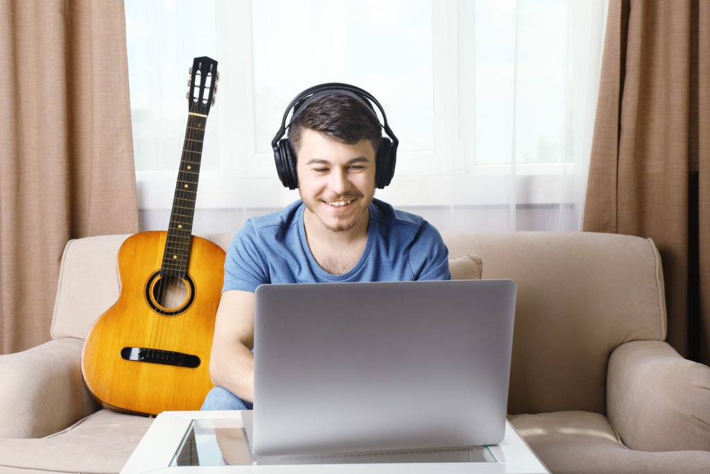 Young man taking music lessons over Skype