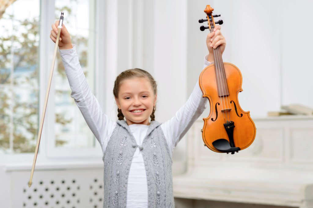 Young student holding up a violin victoriously